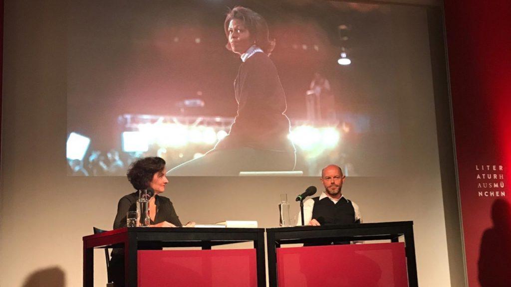 Julia Cortis und Christian Baumann auf der Bühne des Münchner Literaturhauses, im Hintergrund ein übergroßes Portrait von Michelle Obama als Projektion.